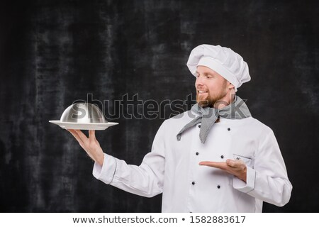 Young smiling chef in uniform looking and pointing at cloche with cooked meal Stock photo © pressmaster