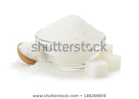 Glass bowl of natural white sugar cubes on white background. Stock photo © DenisMArt