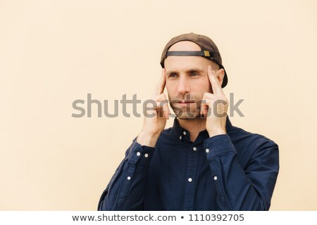 Pensive European male keeps fore fingers on temples, tries to concentrate and recollect his mind, is Stock photo © vkstudio