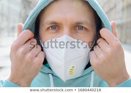 Close up shot of European man protects face with respiratory mask, wears hoodie, poses outdoor on st Stock photo © vkstudio