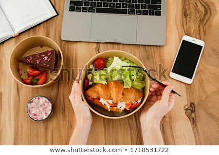 Lunch break concept. Woman with takeout food by her workspace. L Stock photo © dashapetrenko