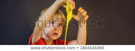 Boy playing hand made toy called slime. Child play with slime. Kid squeeze and stretching slime BANN Stock photo © galitskaya
