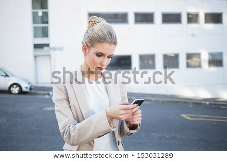 Young fair-haired woman sending text message Stock photo © photography33