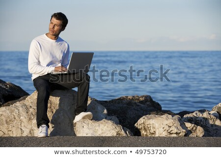 Contemplative man with a laptop by the ocean Stock photo © photography33