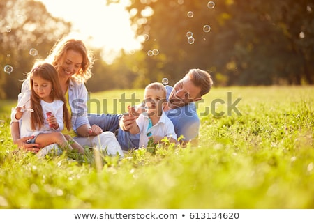 mother with children on grass and bubbles Stock photo © Paha_L