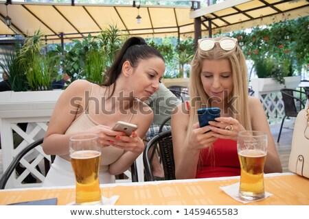 два · женщины · глядя · смартфон · улыбаясь - Сток-фото © rob_stark