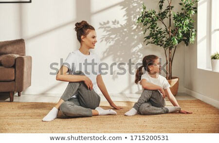 adorable woman in sports wear sitting on the floor stock photo © stockyimages