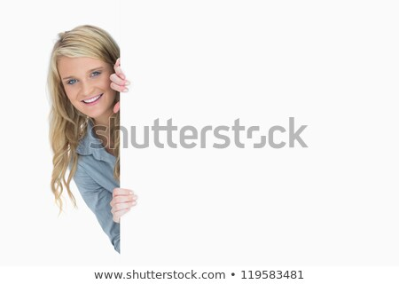 Blonde hiding behind a poster while holding it Stock photo © wavebreak_media