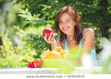 happy smiling young woman eating organic apple at her garden stock photo © hasloo