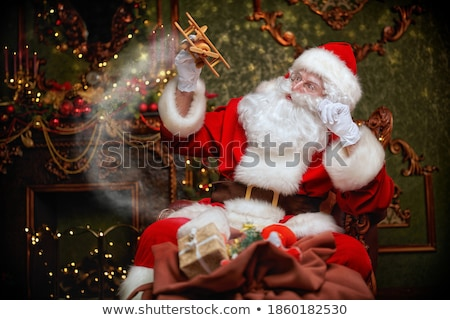 Santa Claus sitting and playing with toys Stock photo © HASLOO