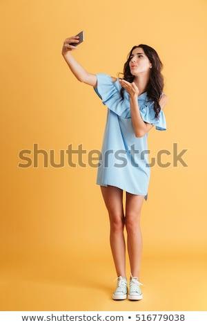 uśmiechnięty · młoda · kobieta · Fotografia · smartphone · szary - zdjęcia stock © deandrobot