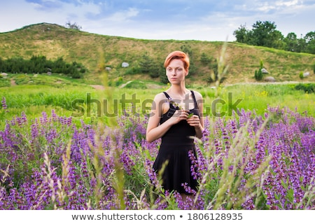 Stock photo: Portrait of a young redhead woman with mountains on background