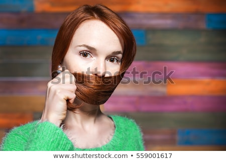 Pretty woman with freckles covering her mouth Stock photo © Aikon