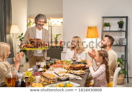 Young children at party sitting at table with mother carrying ca Stock photo © monkey_business