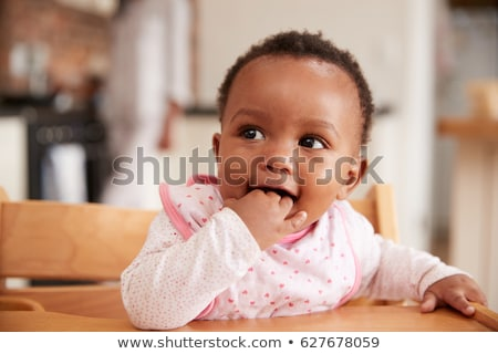 A baby girl in a high chair stock photo © IS2