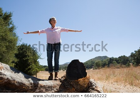 Senior woman standing on a log with open arms Stock photo © IS2