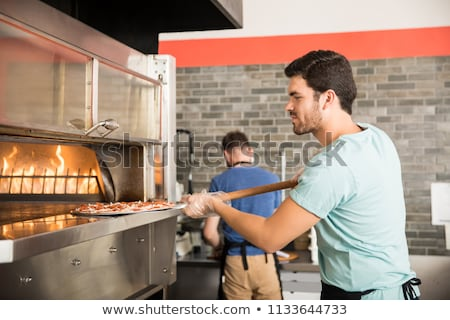 man with peel placing pizza to oven at pizzeria Stock photo © dolgachov