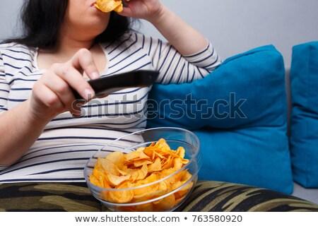 женщину еды картофельные чипсы Смотря телевизор расслабляющая диван Сток-фото © AndreyPopov