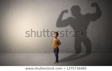 Muscleman shadow behind waggish little boy Stock photo © ra2studio