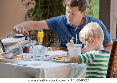 family of two eating nicely served breakfast outside handsome young man pouring some coffee and his  Stock photo © galitskaya