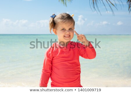 Smiling Girl Pointing Her Finger Upward At Beach Stock photo © AndreyPopov