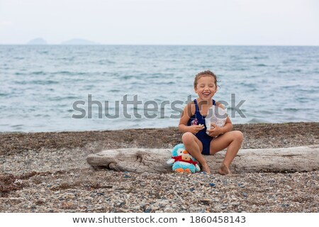 Girl sitting on a log at the beach Stock photo © galitskaya
