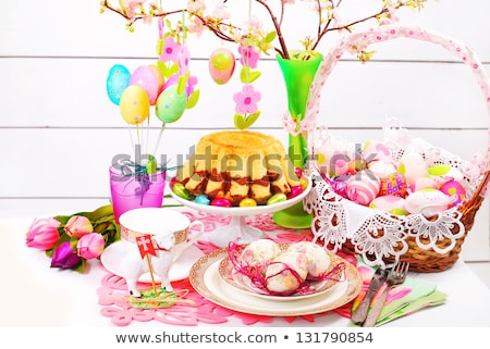 easter eggs in basket, plates, cutlery and flowers Stock photo © dolgachov