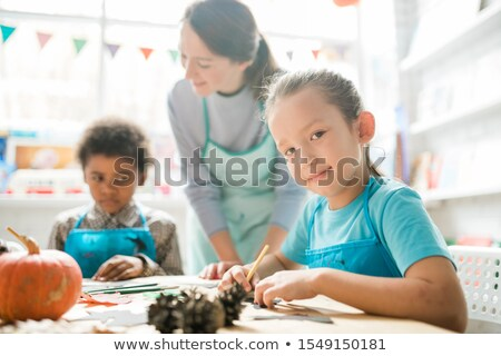 Cute schoolgirl looking at you on background of teacher and one of classmates Stock photo © pressmaster