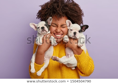 Horizontal shot of happy Afro American woman spends leisure time with dog, feels comfort, poses on b Stock photo © vkstudio
