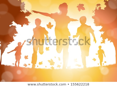 Stock photo: A cheerful child walks in the autumn in a garden with trees covered with a yellow leaf