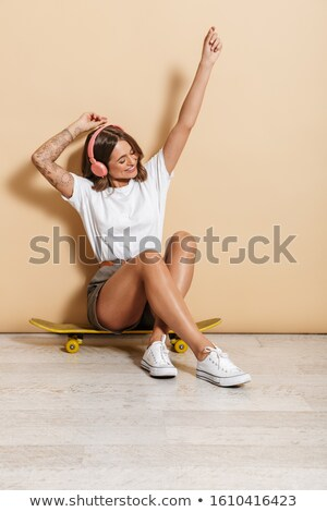 Image of teen girl in headphones rejoicing while sitting on skat Stock photo © deandrobot