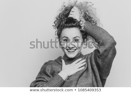 Adorable excited young female with curly hair, keeps hair tied in pony tail, dressed in casual red s Stock photo © vkstudio