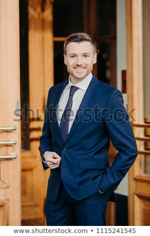 Vertical shot of handsome unshaven male employee has cheerful expression, dressed in elegant suit, s Stock photo © vkstudio