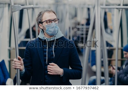 Pensive young man in eyewear wears protective surgical mask during coronavirus outbreak, poses in pu Stock photo © vkstudio