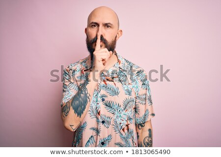 tattooed man with finger on mouth Stock photo © diego_cervo