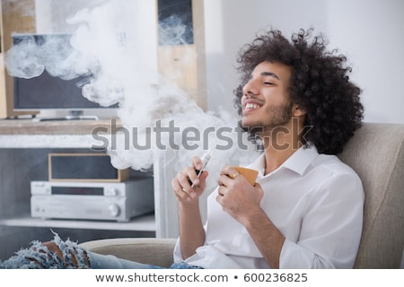 portrait of a young man drinking coffee while sitting on armchai stock photo © hasloo