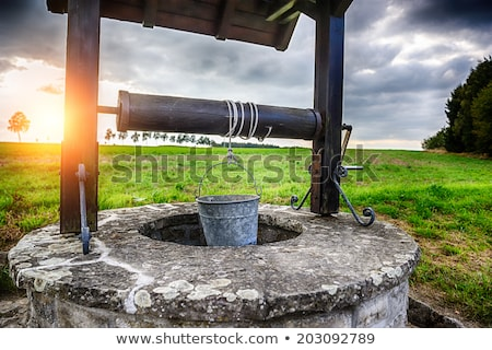 landscape with old wooden well and bucket of water Stock photo © LoopAll