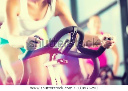 Junge Fitnessfrau auf dem Fahrrad Stock foto © Kzenon