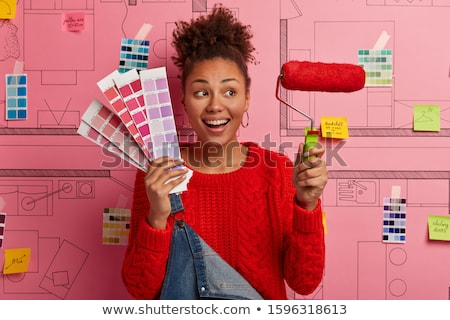 Rejoicing woman holding a paint roller Stock photo © photography33