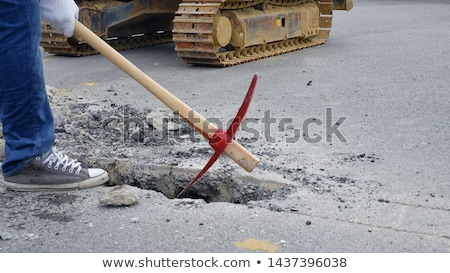 Construction worker holding a glove and pickaxe Stock photo © photography33