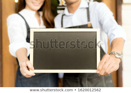 Young Woman Holding Up A Small Blank Blackboard Stok fotoğraf © vichie81
