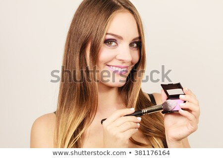Woman applying blush to her cheekbones Stock photo © photography33