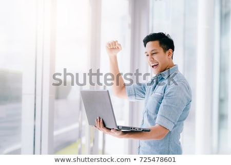 Excited Asian man using laptop Stock photo © szefei