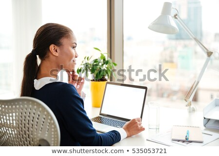 Stok fotoğraf: Thoughtful Woman In Black Dress Sitting On The Office Chair Over Gray Background
