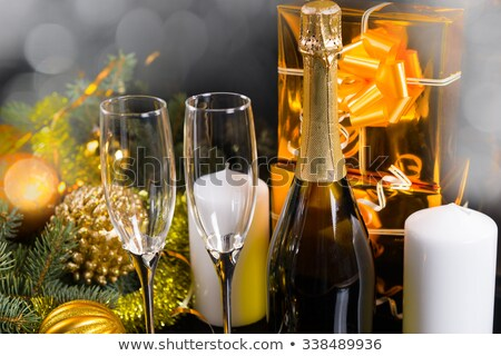 two glasses with champagne, old pocket watch, streamer, cork and confetti in front of a champagne bo Stock photo © Rob_Stark