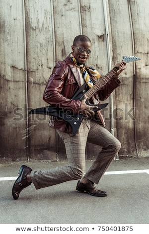 Stock photo: young guitarist in leather jacket playing