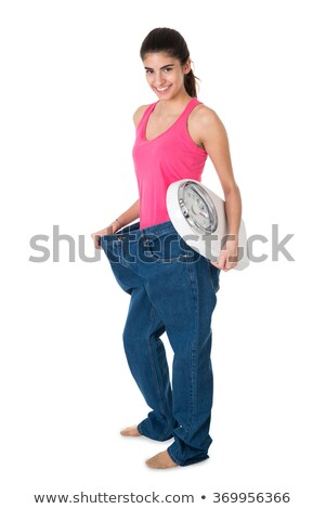 smiling woman with weight scale showing her old jeans stock photo © andreypopov