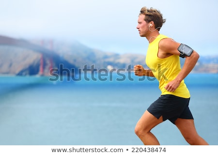 Stock photo: Man running with earphones and smartphone.