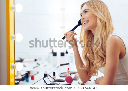 Side view woman sitting by table and looking at mirror Stock photo © deandrobot