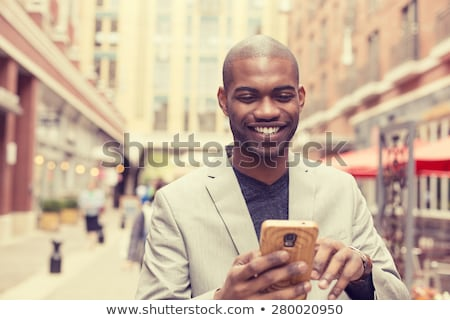 happy smiling urban businessman using smart phone outside stock photo © boggy
